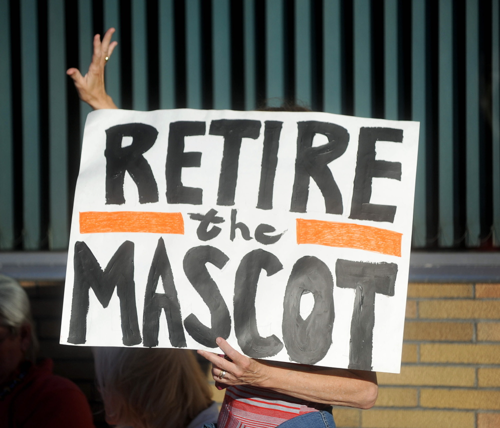 A woman holding a sign urging Skowhegan to change the mascot at the local high school waves on Thursday to a supporter in Skowhegan.