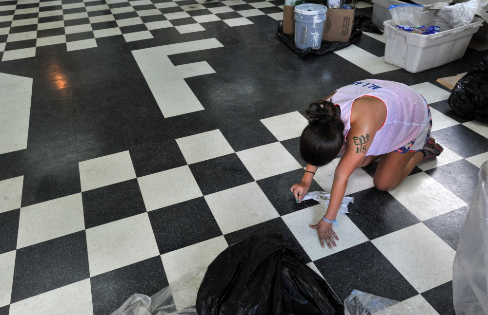 Noel Allan, 16, of Center Valley, Pennsylvania, cleans paint drops from the floor Thursday at the North Anson Fire Station. A group of volunteers put a fresh coat of paint on the station.