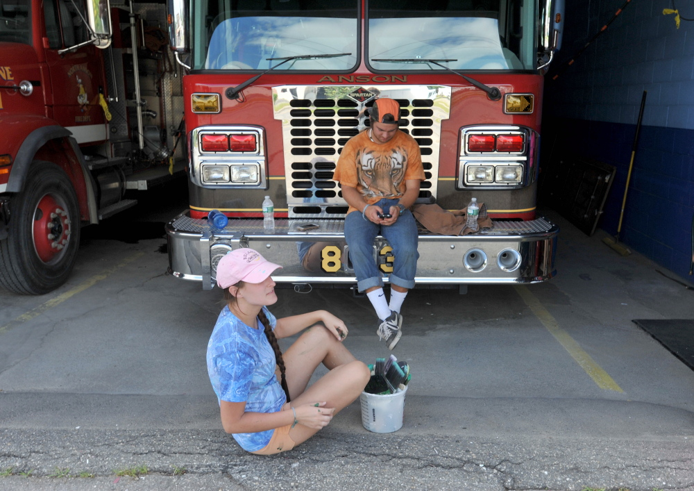 Charlie Grim, 23, and Luke Pukanecz, 17, take a break Thursday after a day of painting the North Anson Fire Station.