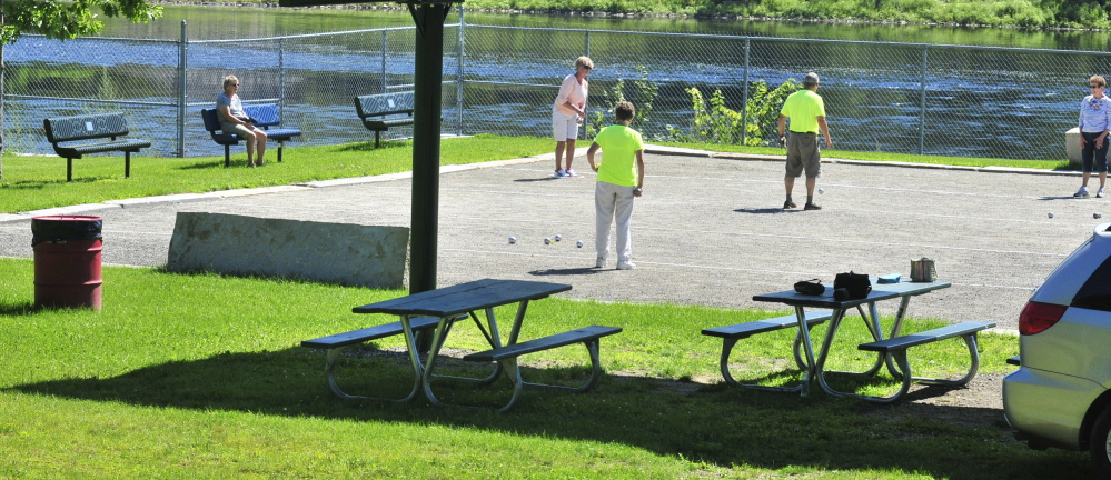 People play petanque Saturday at Mill Park in Augusta. The city is considering replacing the high chain-link fence behind them with a shorter one and building a mile-long looped walking path around the park's perimeter, affording views of the Kennebec River.