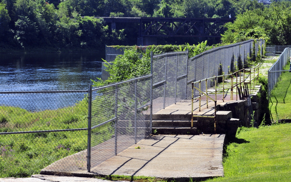 This 8-foot-high chain-link fence between Mill Park and the Kennebec River, seen Saturday in Augusta, might be replaced by a more attractive and shorter one. The City Council plans to discuss that idea and other capital improvement projects Monday, including building a mile-long looped walking path around the park's perimeter.
