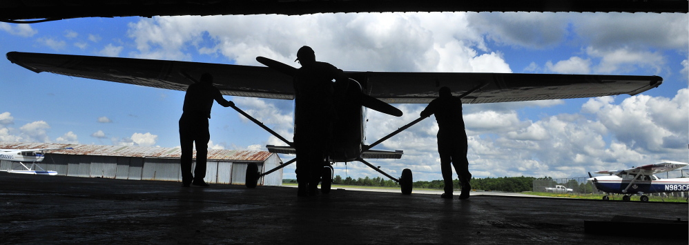 Civil Air Patrol senior members push a plane out of the group's hangar Saturday at the Augusta State Airport. Two pilots were going to use the plane to look for forest fires.