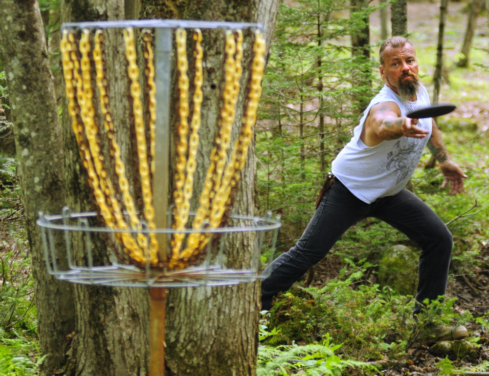 Charlie Wilson throws towards the basket while playing the short nine hole putt course at DND Disc Golf on Thursday in Sidney.