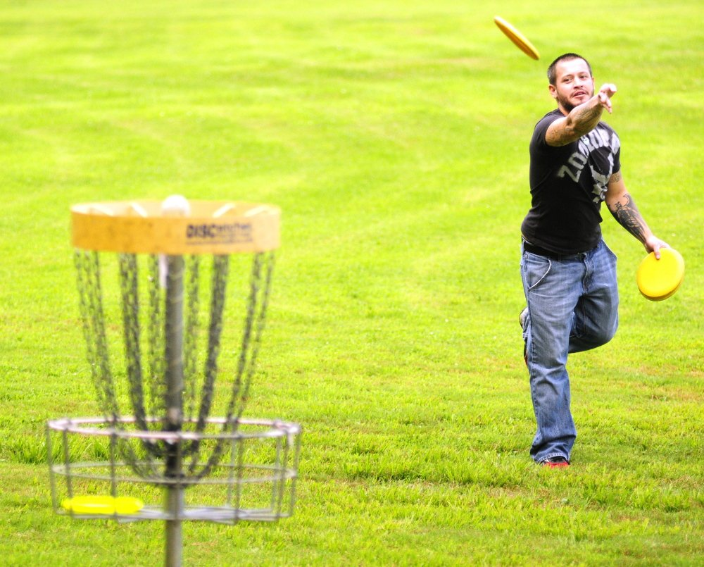 Joseph Stevens tosses discs on the putting green before league play at DND Disc Golf in Sidney.