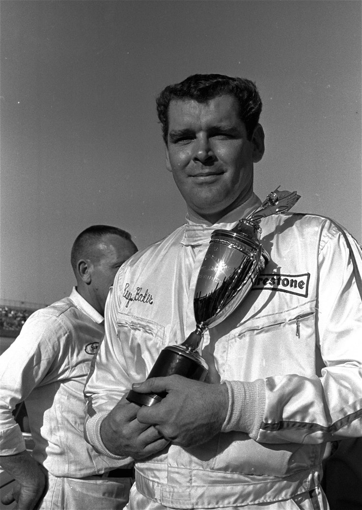 In this Feb. 9, 1969, file photo, Buddy Baker  holds a trophy presented to him after he won the pole position for the Daytona 500 Grand National stock car race at Daytona Speedway in Daytona Beach, Fla.