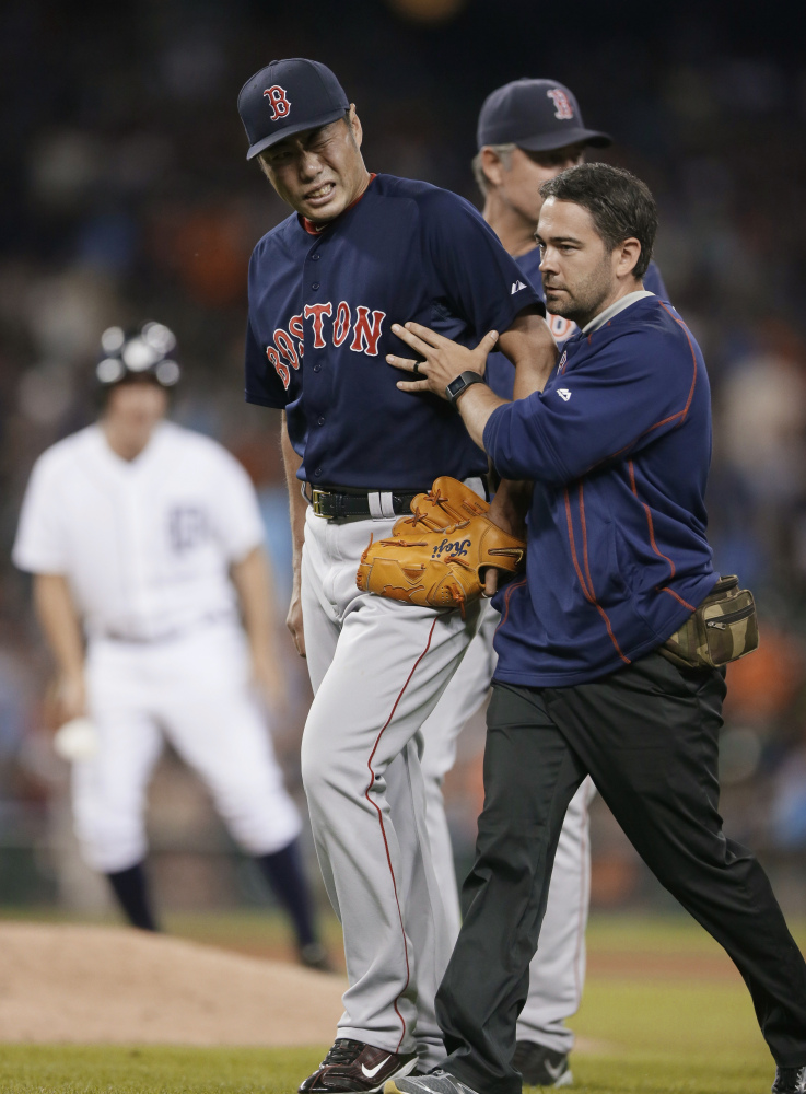 Boston Red Sox relief pitcher Koji Uehara is helped off the field after a game against the Detroit Tigers last week in Detroit. Uehara is out for the rest of the season with a broken wrist.