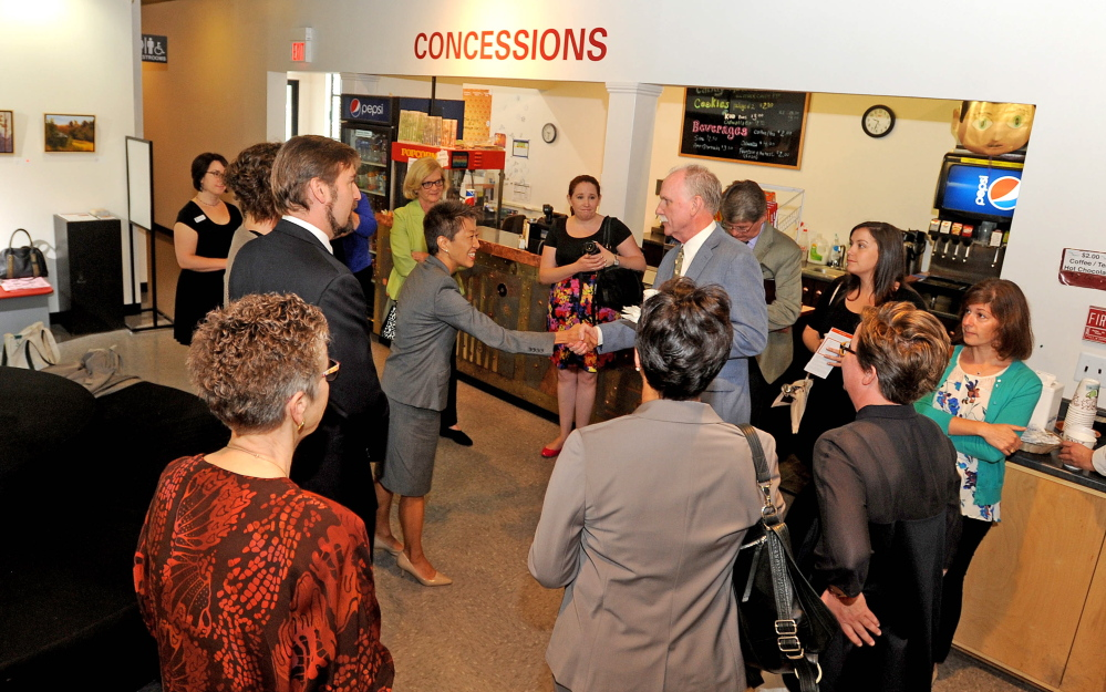 Jane Chu, chairman of the National Endowment of the Arts, left center, is greeted in the lobby of Railroad Square cinemas during a special meeting with local arts groups in Waterville on Tuesday.