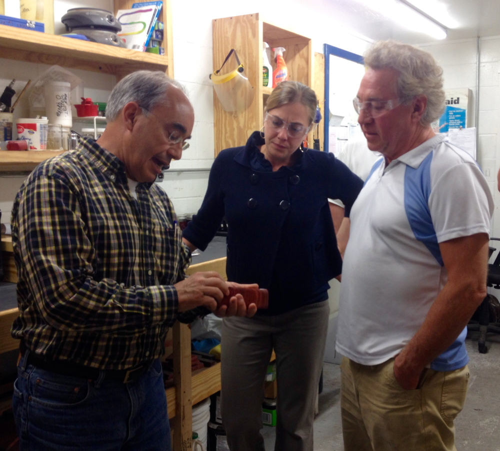 U.S. Rep. Bruce Poliquin, a Republican from Maine's 2nd District, looks at a product made by Cousineau Wood Products in North Anson with Samantha Warren, his district director. At right is Randy Cousineau, the company's CEO.