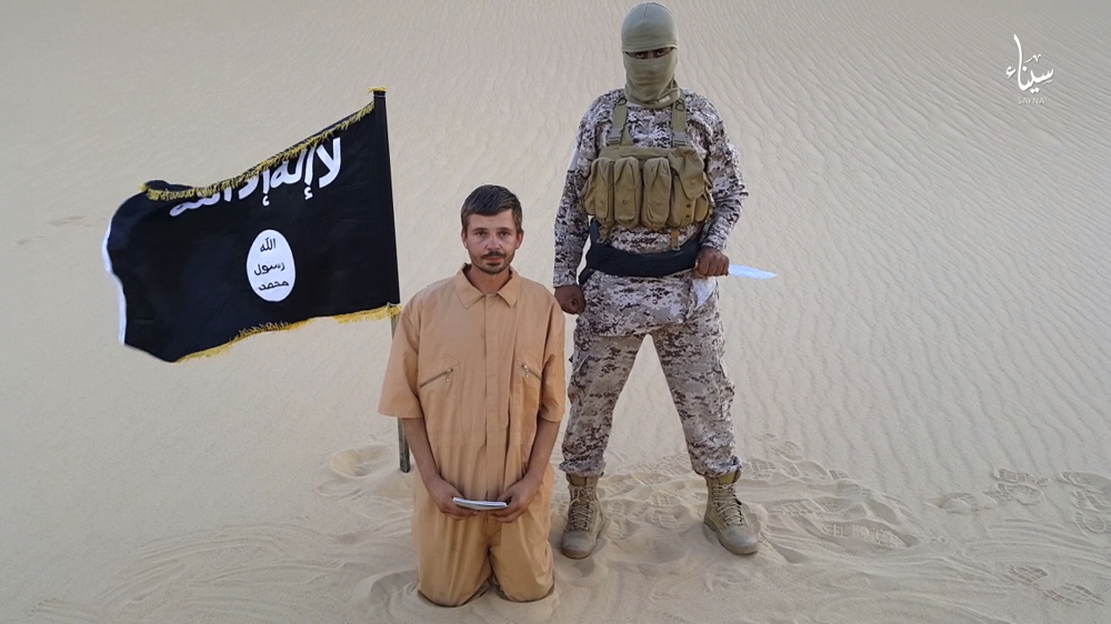 This image made from a militant video posted on a social media site on Wednesday, Aug. 5, 2015, which has been verified and is consistent with other AP reporting, purports to show a militant standing next to another man who identifies himself as 30-year-old Tomislav Salopek, kneeling down as he reads a message at an unknown location.