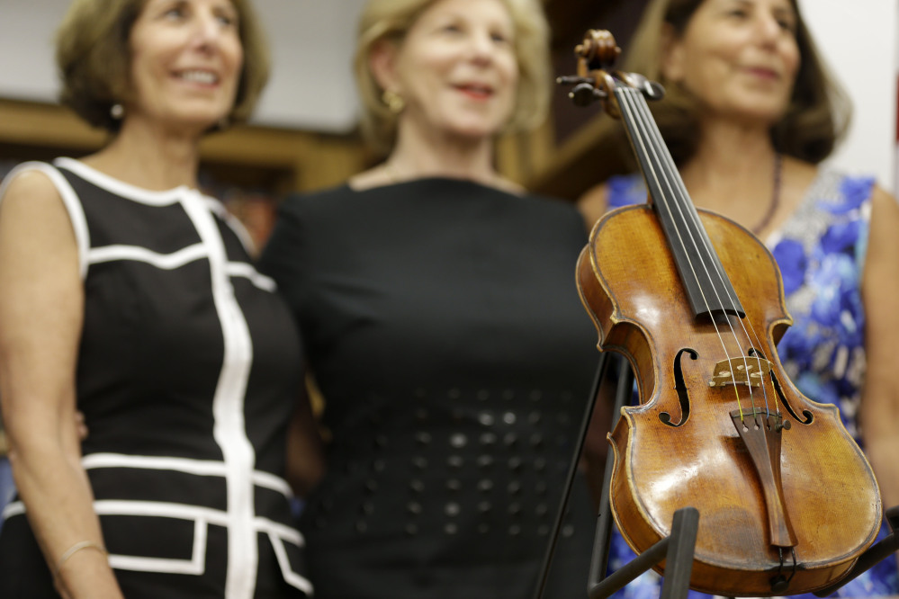 Sisters Jill Totenberg, left, Nina Totenberg, center, and Amy Totenberg pose for pictures with the recovered Ames Stradivarius violin during a news conference in New York, Aug. 6.