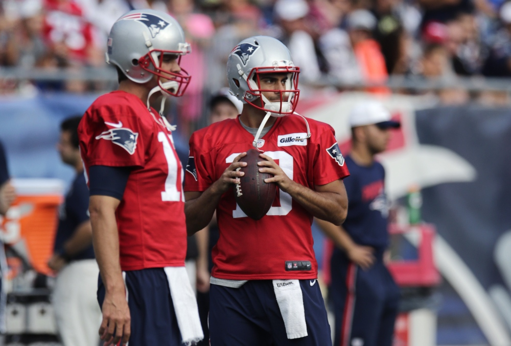 In this Aug. 5 photo New England Patriots quarterback Jimmy Garoppolo, right, clutches the football as he stands with Tom Brady at training camp in Foxborough, Mass.