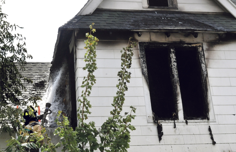 Waterville firefighter Richard Haviland sprays water through a window into the heavily damaged second floor of a home on Silver Street in Waterville on July 29. Officials still haven't determined the cause of the fire.