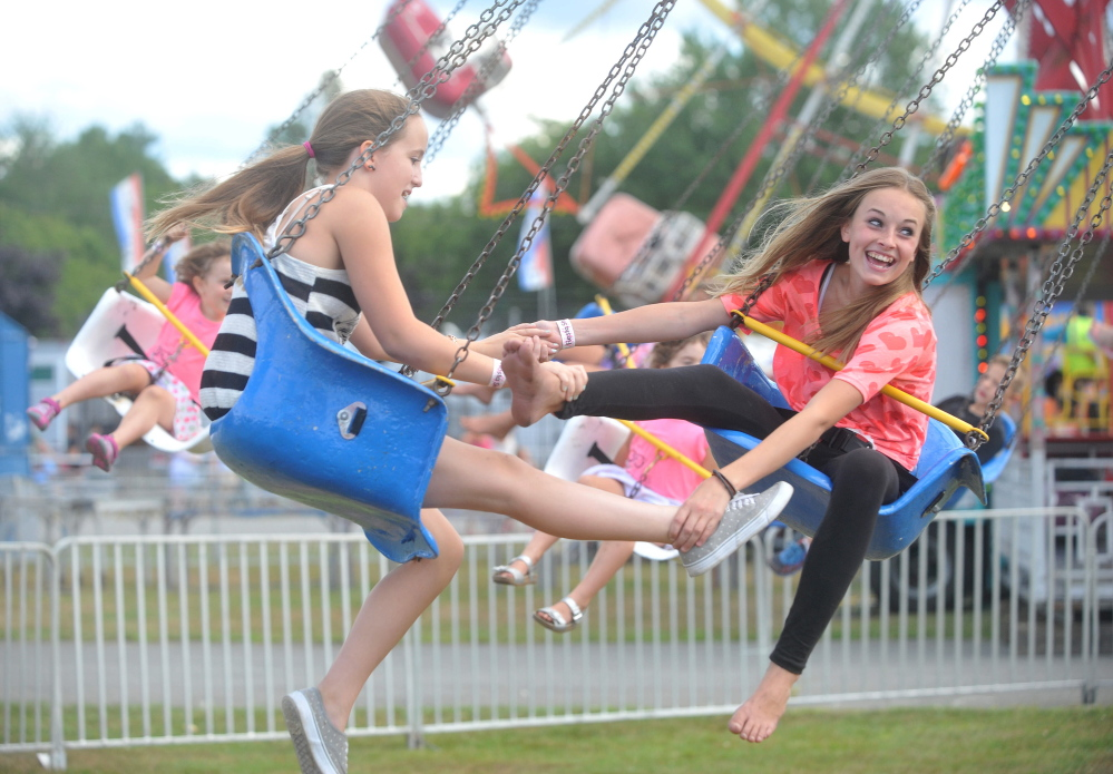 Ellis Sirois, 12, left, and Ashley Corson, 13, right, ride the trapeze swing Thursday on the opening day of the Skowhegan State Fair.