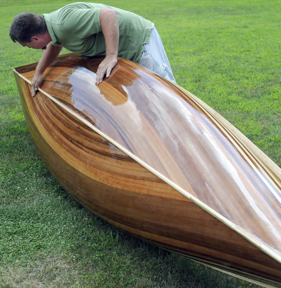 Math teacher Jeromy Jamison inspects the hull of the cedar strip canoe he built with his Hall-Dale middle  and high school students at his home in Windsor.