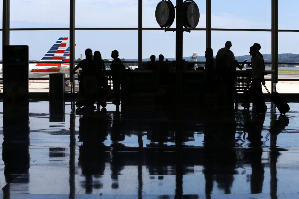 People ask questions at an information kiosk at Washington's Reagan National Airport after technical issues at a Federal Aviation Administration caused delays and cancellations on Saturday.