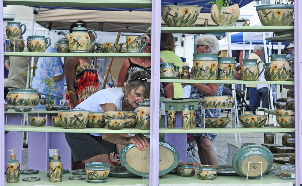 Sue Firlotte, of North Monmouth, picks up a platter on Saturday in The Potter's House booth during the Winthrop Summer Festival in downtown Winthrop.