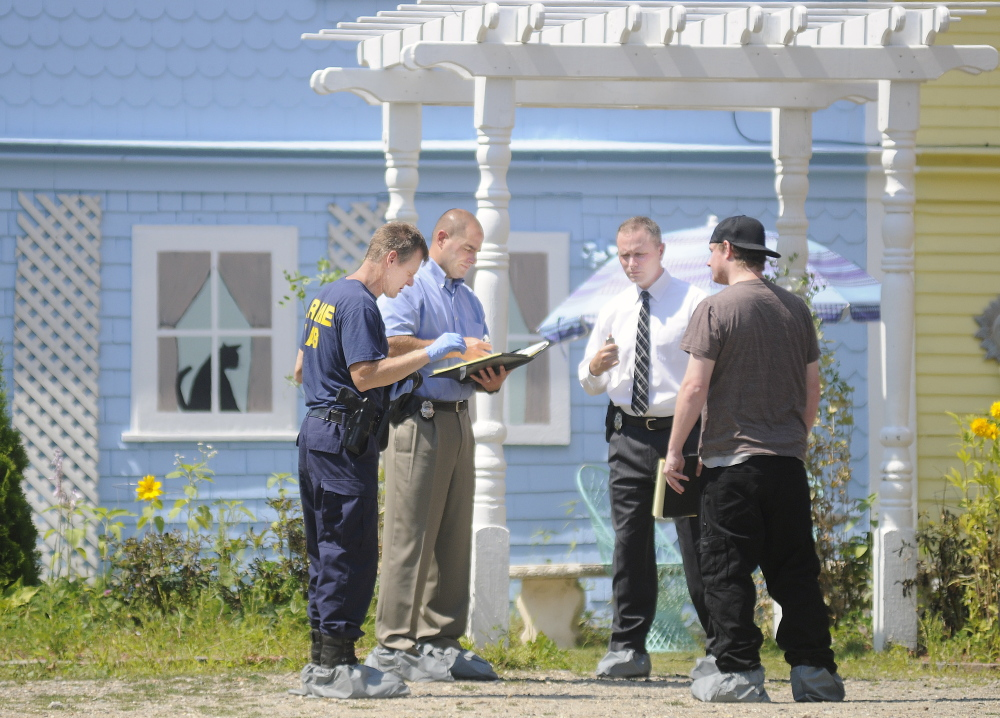 Maine State Police detectives interview a former resident of a boarding house in East Pittston about a stabbing that occurred on Saturday.