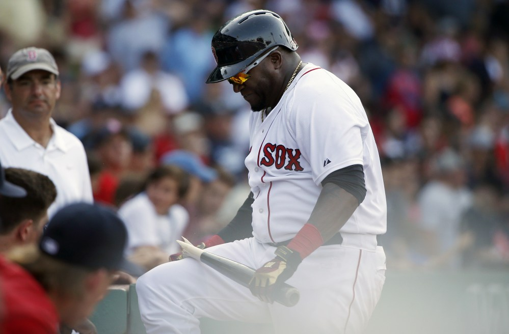 Boston Red Sox designated hitter David Ortiz breaks his bat over his knee after striking out during the eleventh inning against the Seattle Mariners on Sunday in Boston. The Mariners won 10-8.