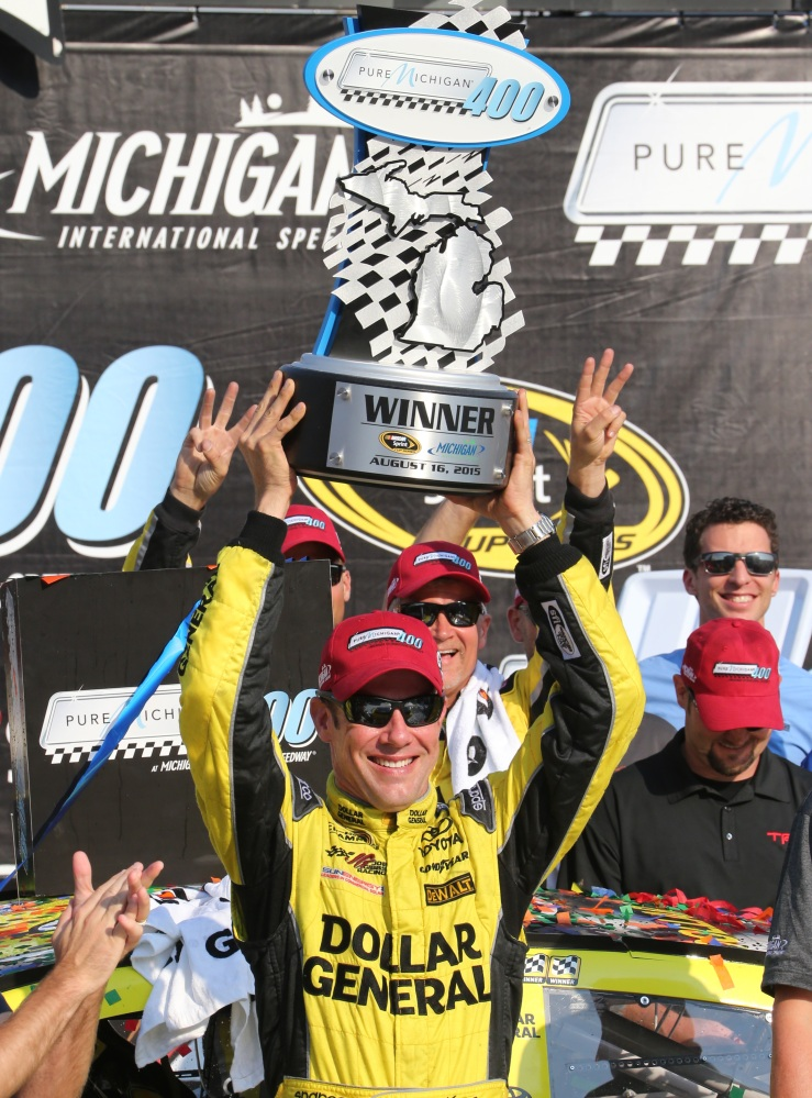 Matt Kenseth raises the trophy after winning the NASCAR Sprint Cup series race at Michigan International Speedway on Sunday in Brooklyn, Mich.