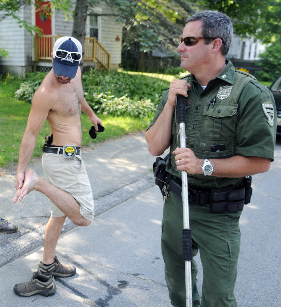 Jared Stevens inspects his foot Monday after a gray fox bit him on the steps of his Monmouth home. District Game Warden Steve Allarie searched for the animal that also bit another person. Stevens put a pistol in his waistband after the attack.