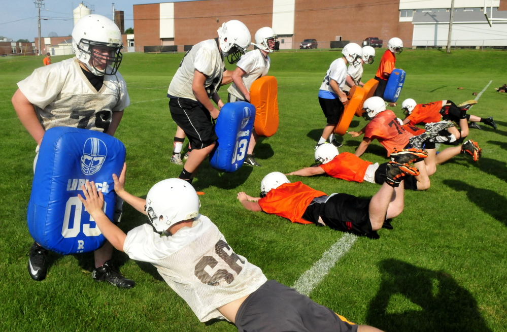 Skowhegan Area High School football players go through defensive drills during practice Monday in Skowhegan.