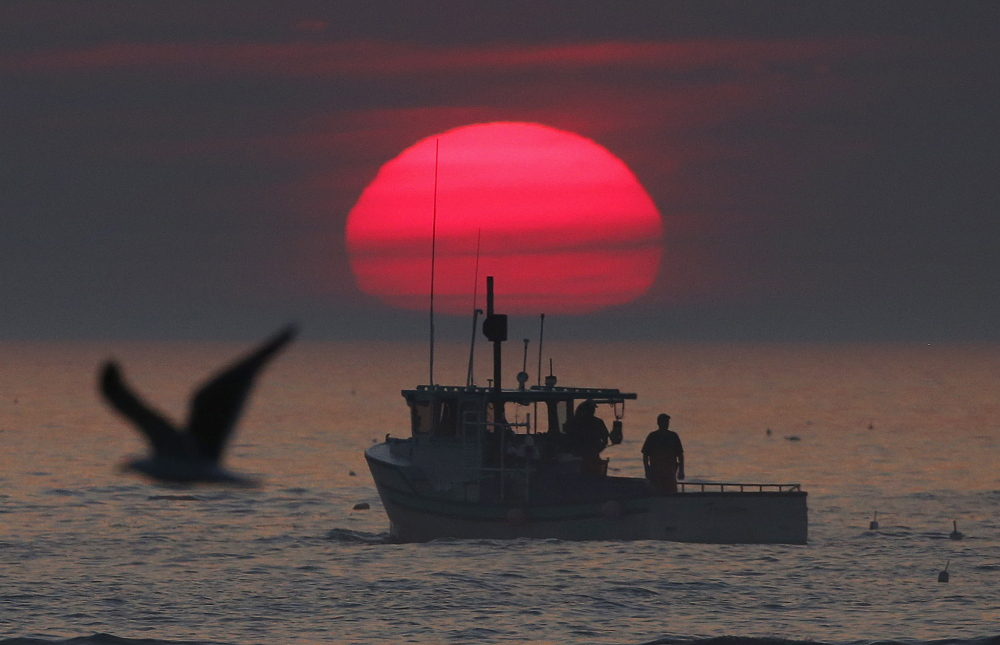 A lobster boat heads out to sea at sunrise, off Kennebunkport.