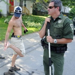 Jared Stevens inspects his foot Monday after a gray fox bit him on the steps of his Monmouth home. District Game Warden Steve Allarie searched for the animal, which also bit another person. Stevens put a pistol in his waistband after the attack.