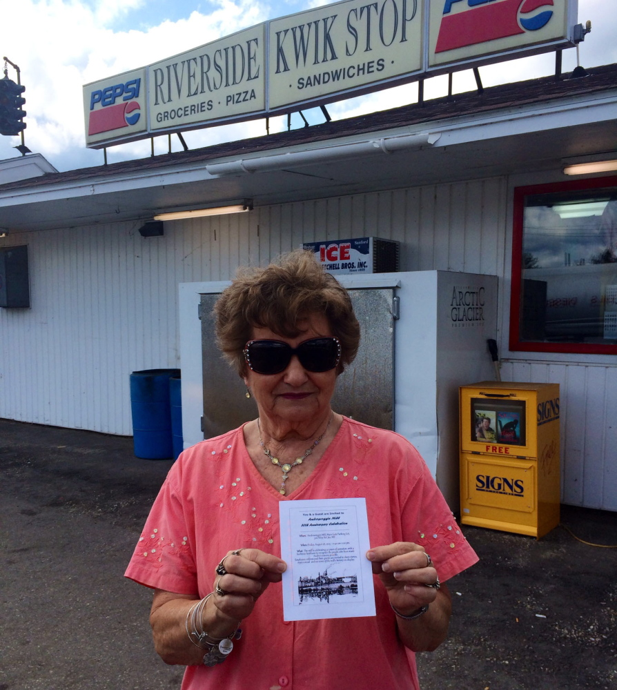 Glenda DiPompo shows a flier she got in the mail Thursday inviting her to a celebration of the mill's 50th anniversary. DiPompo, whose husband retired from the mill and whose son works there, owns Riverside Kwik Stop and says the layoffs will hurt business.