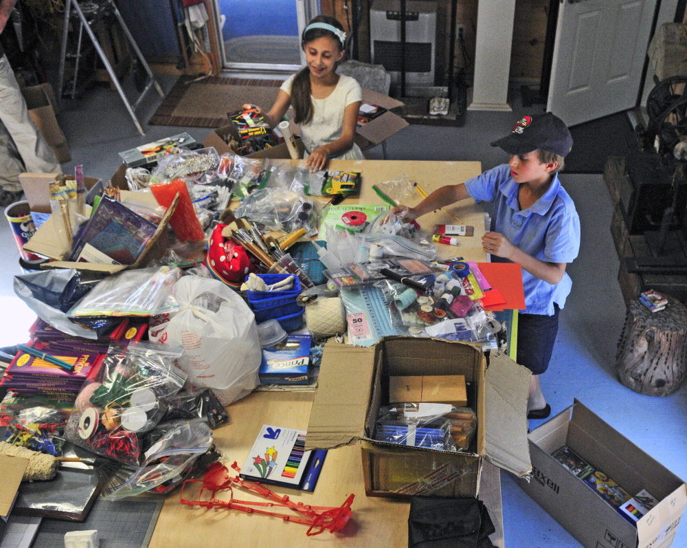 Ten-year-old twins Noah, left, and Ava Katz pose recently with the art supplies they collected and plan to donate to the Crow Indian Reservation in Montana.