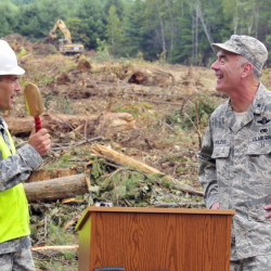 Lt. Col. Norm Michaud, project manager, jokes about using a smaller shovel, before Brig. Gen. Gerard Bolduc, adjutant general of Maine National Guard, used a large excavator during a ceremonial ground breaking for new headquarters on Thursday in Augusta.