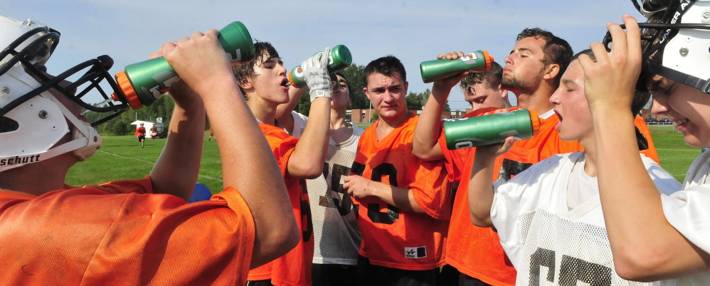 Staff photo by David Leaming   Members of the Skowhegan football team cool off during practice Monday. The team took regular breaks as high heat and humidity gripped the region.