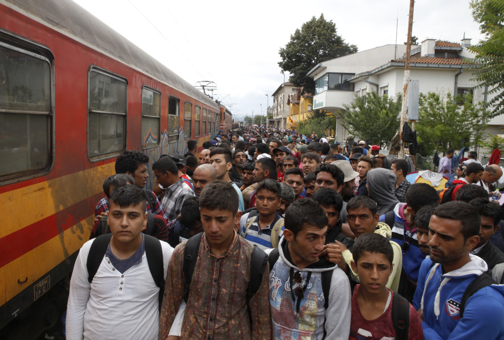 Migrants line up to board a train that will take them toward Serbia, at the railway station in the southern Macedonia's town of Gevgelija on Saturday.