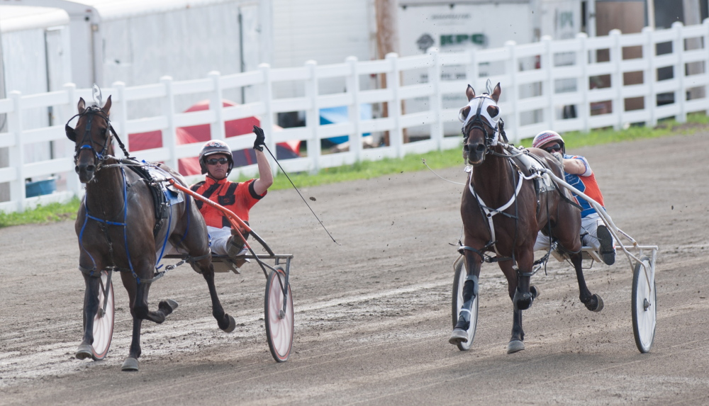 Kevin Bennett photo   Heath Campbell, left, riding Wheelaway, crosses the finish line ahead of Warrawee Nonsuch and driver David Ingraham on Saturday to win the annual Walter H. Hight Invitational at the Skowhegan Fairgrounds.