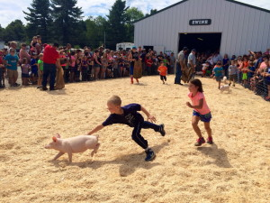 Drake Dumont, 7, of Albion, outruns Lilly Kinney, 6, of Cornville, in an effort to catch a pig Saturday at the Skowhegan State Fair pig scramble.