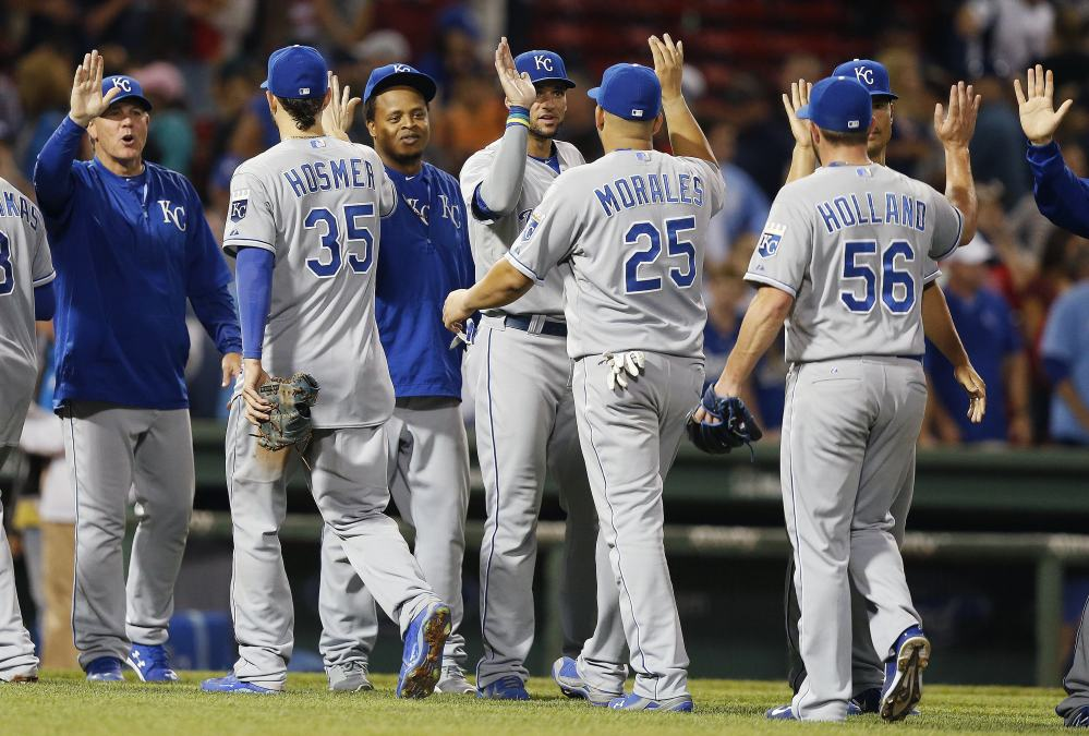 AP photo   The Kansas City Royals, including Greg Holland (56), Kendrys Morales (25) and Eric Hosmer (35), celebrate after defeating the Boston Red Sox 6-3 on Saturday.