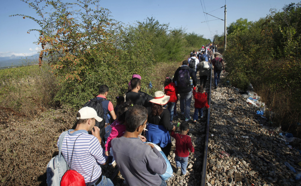 Migrants walk along the railway tracks after crossing from Greece to Macedonia, at the border line between the two countries, near southern Macedonia's town of Gevgelija on Sunday.