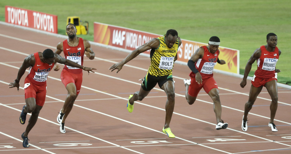 Jamaica's Usain Bolt, center, crosses the finish line to win the gold medal in the men's 100m ahead of United States' Justin Gatlin, left, at the world championships in Beijing on Sunday.