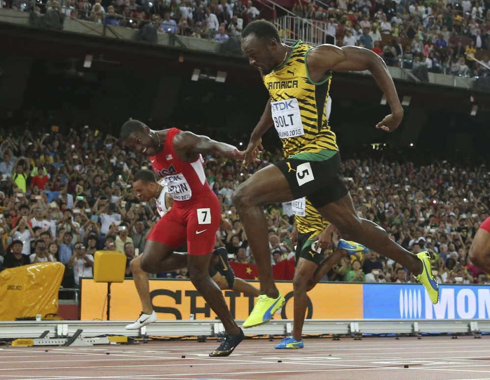 Jamaica's Usain Bolt crosses the finish line to win the men's 100-meter final at the world championships at Beijing on Sunday. United States' Justin Gatlin, left, was second.