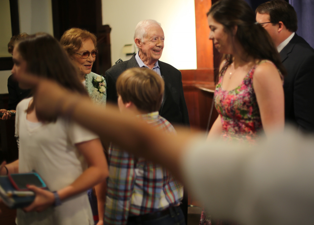 Former President Jimmy Carter, center, and Rosalynn Carter greet the visitors who attended the Sunday school he taught Sunday morning in Plains, Georgia.