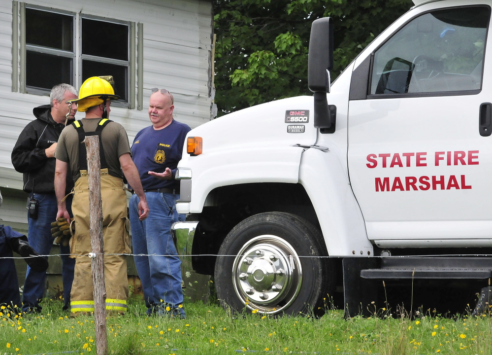 Investigator Kenneth MacMaster, right, of the Office of the State Fire Marshal, speaks with Oakland fighters outside the burned mobile home at 146 Ten Lots Road in Oakland on Sunday. A male occupant was reportedly transported to the hospital with serious injuries.