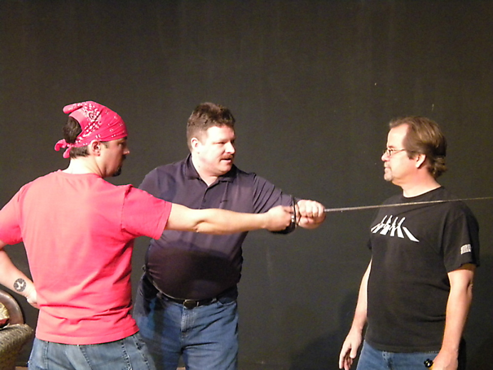 Instructor Jeffrey Eagen, center, shows actors James Paine, left, and Bart Shattuck, right, proper combat technique during training for the Aqua City Actors Theater.