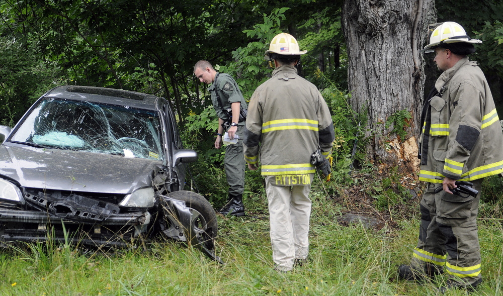 Police and firefighters examine the scene of an accident on Route 194 in Pittston that injured a teenage driver on Tuesday.