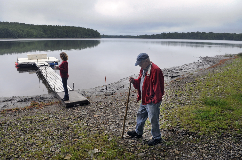 Stan Whittier walks on the shore of Clary Lake in Jefferson earlier this month while his daughter, Jane Roy, stands on the family's dock. It's been nearly three years since property owners around the lake in Jefferson and Whitefield appealed to the state to intervene over a low water level, and residents say the situation still hasn't improved.