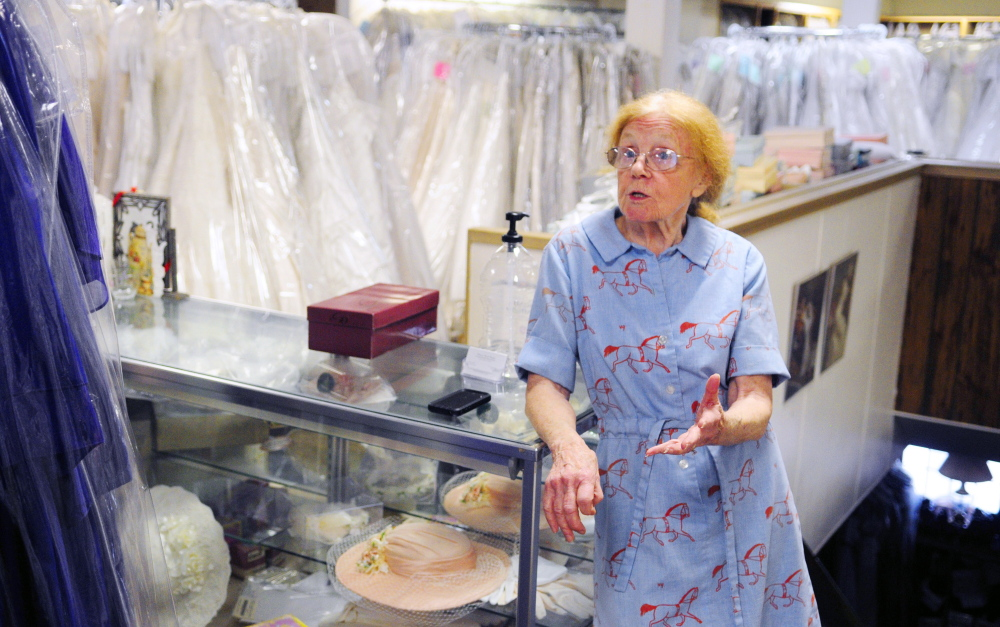 Patricia Buck, owner of Patricia Buck Bridal, talks about plans for a new owner to buy and renovate 275 Water St. during an interview on Tuesday at the shop, which is being forced to close by the city because of safety concerns.