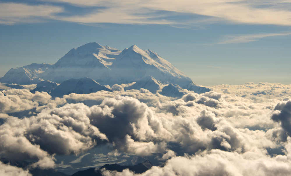 In this Monday, Aug. 3, 2015, aerial photo provided by Holland America Line, Mount McKinley pierces through the clouds above Denali National Park and Preserve in Alaska.