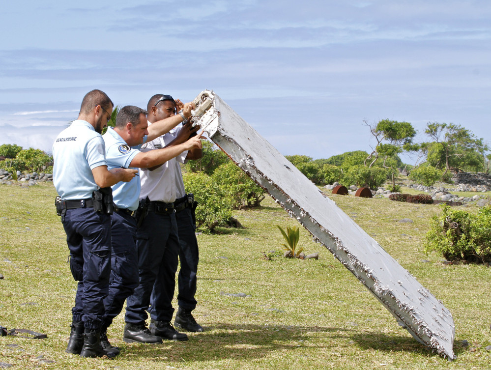 """On July 30, French police inspect the wing piece found on Reunion Island that is now confirmed to be the """"flaperon"""" of Malaysian Flight 370. The Associated Press"""