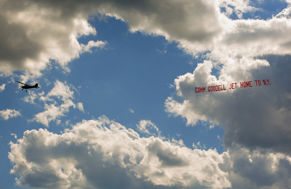 """A plane tows a banner with the message """"Comm. Goodell Jet Home to N.Y."""" over Biddeford Municipal Airport on Sunday."""
