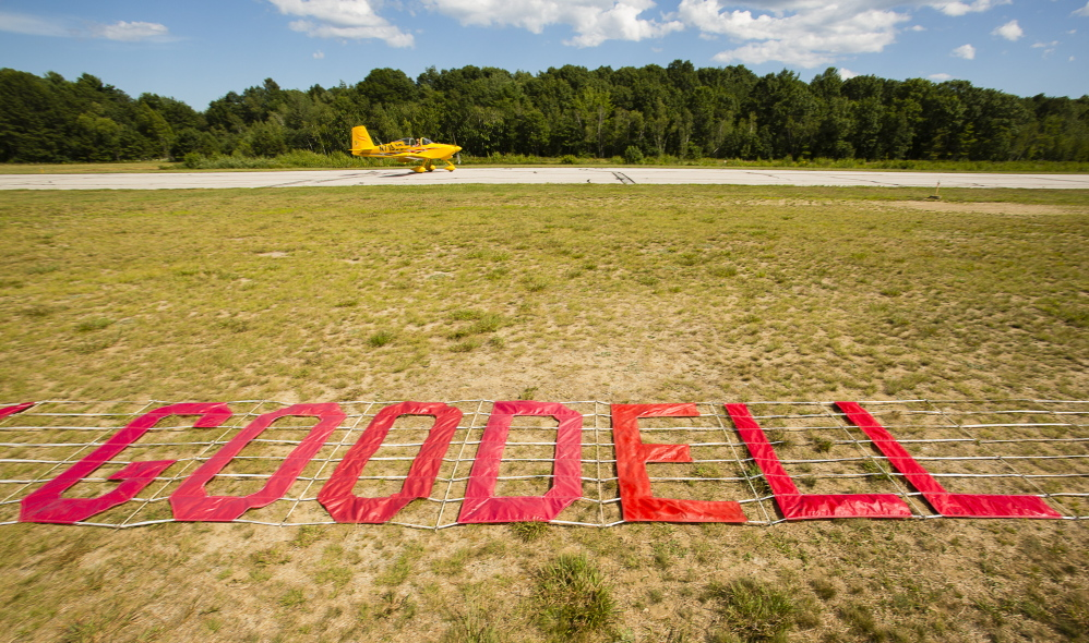 """A banner with the message """"Comm. Goodell Jet Home to N.Y."""" waits to be picked up and towed by a plane at Biddeford Municipal Airport on Sunday."""