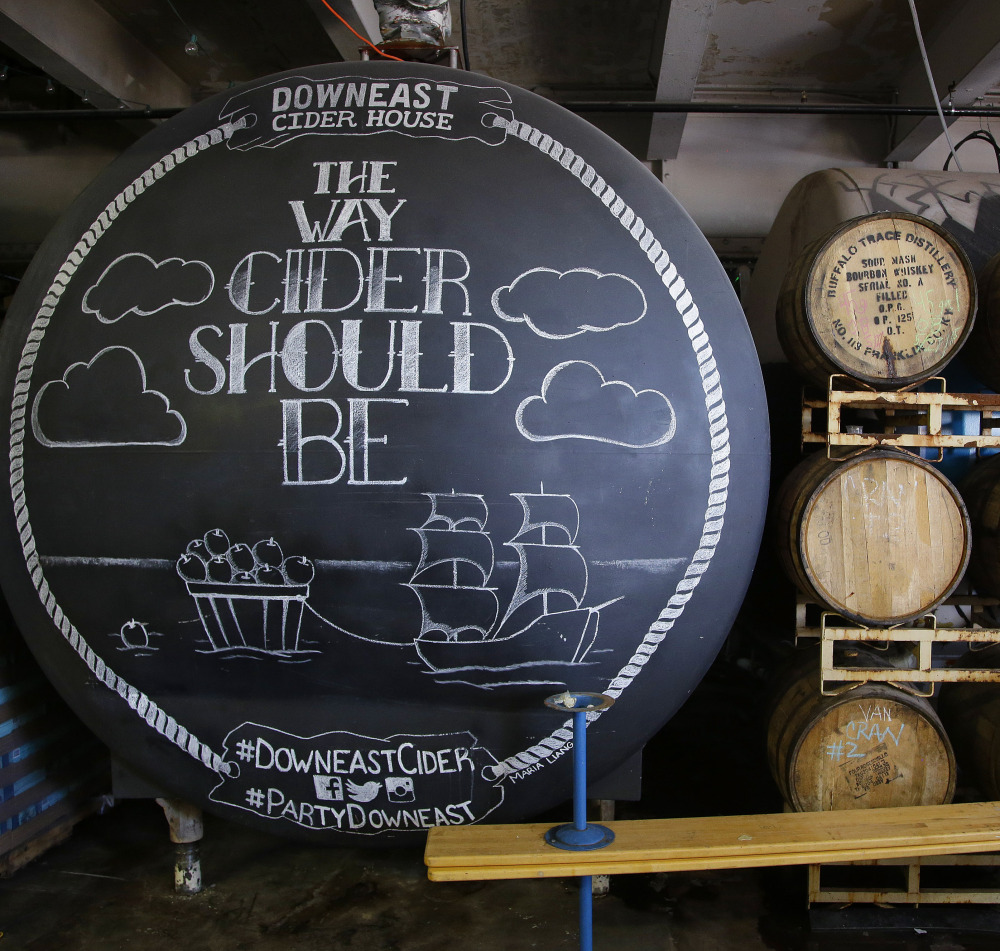 A storage tank and wooden whiskey barrels hold hard cider at Downeast Cider House in Boston. The company expects to produce 17,000 barrels of cider this year.
