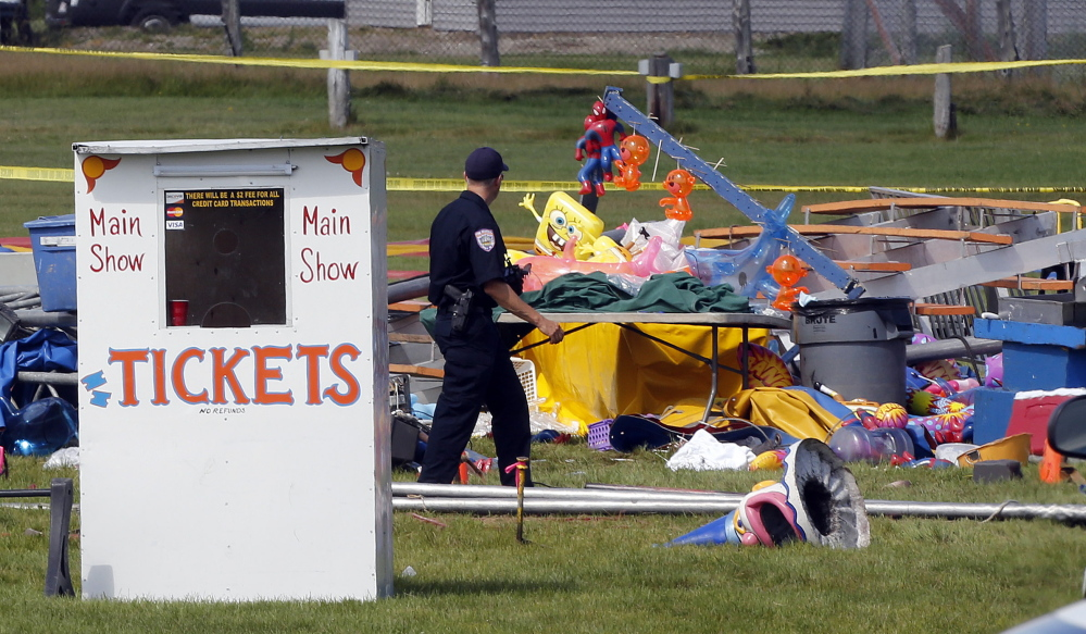 Investigators inspect the site Tuesday where a tent collapsed a day earlier during a Walker International Events circus at the Lancaster Fairgrounds in Lancaster, N.H. A Vermont father and his 8-year-old daughter were killed and more than 50 people were injured.
